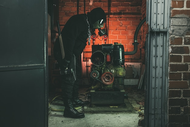 Man with gas mask and a hammer in machine room.