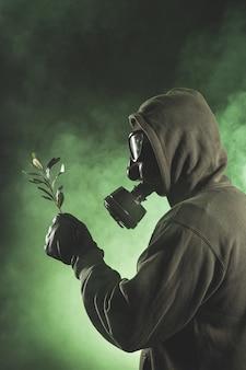 Человек с противогазом держит ветку с листьями
