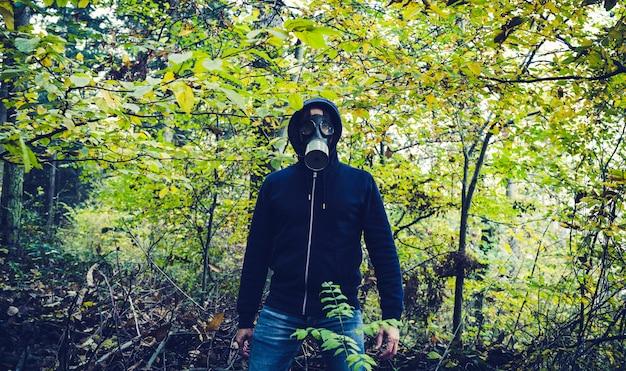가을 숲에서 가스 마스크를 가진 남자