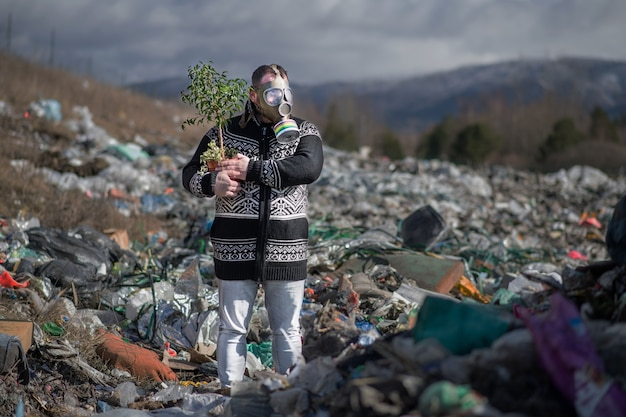 Man with gas mask and potted plant on landfill, environmental concept.