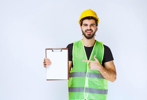 プロジェクトフォルダを保持し、満足のサインを示すギアを持つ男。