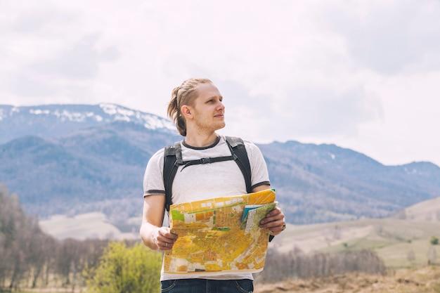 旅行者の手に地理的な紙のカードを持つ男