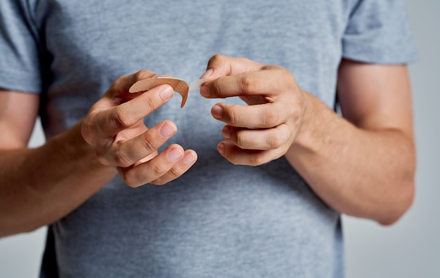 Man with germicidal plaster on finger gray t-shirt isolated background