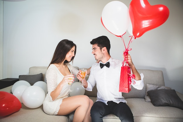 Man with gifts having a drink with his wife Free Photo