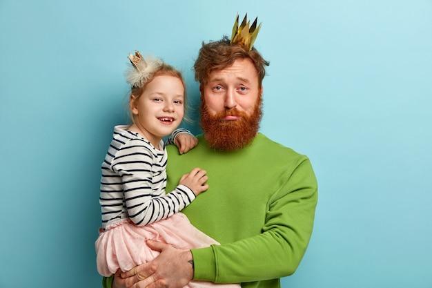 Мужчина с рыжей бородой и его дочь с аксессуарами для вечеринок