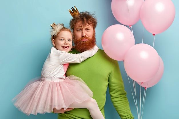 生姜のひげを持つ男とパーティーアクセサリーを持つ彼の娘