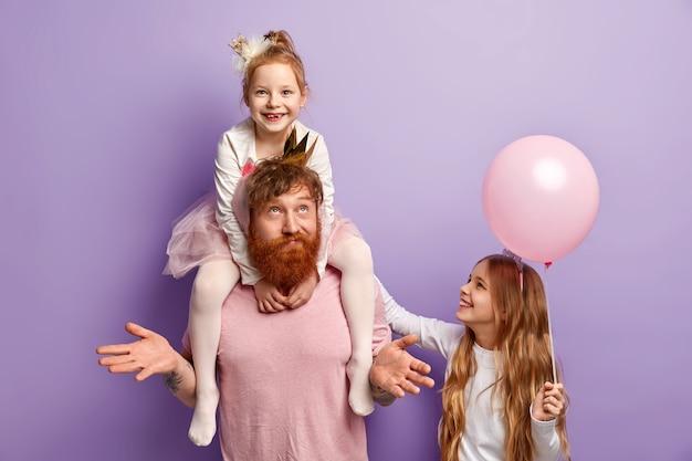 Мужчина с рыжей бородой и его дочери с аксессуарами для вечеринок