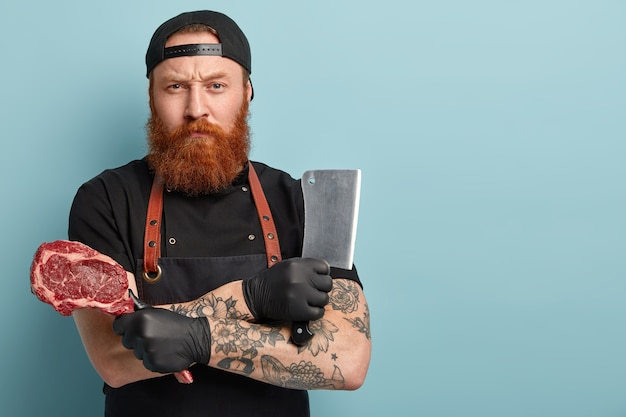 Man with ginger beard in apron and gloves holding knife and meat