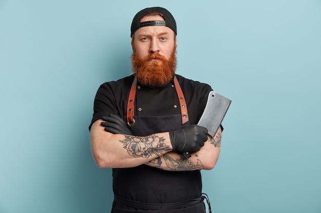 Man with ginger beard in apron and gloves holding knife