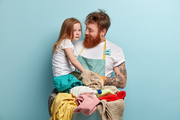 Man with ginger beard doing laundry and holding his daughter