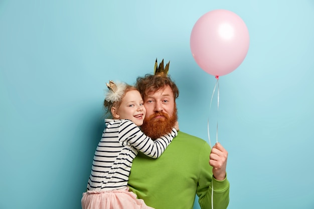Man with ginger beard and his daughter with party accessories