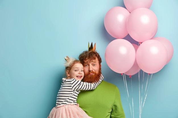 Uomo con la barba allo zenzero e sua figlia con accessori da festa