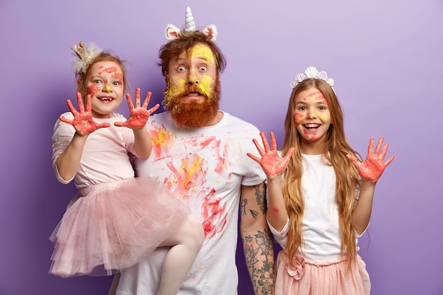 Man with ginger beard and his daughters wearing dirty clothes