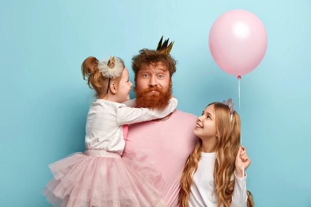 Uomo con la barba allo zenzero e le sue figlie con accessori da festa