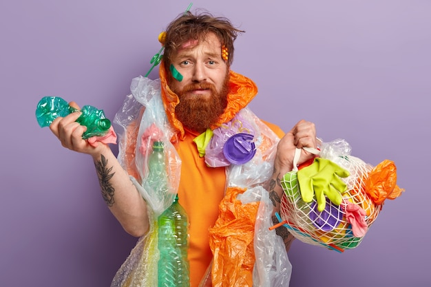 Man with ginger beard holding bags with plastic waste
