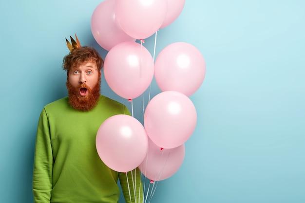Человек с рыжей бородой держит воздушные шары