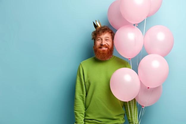 Uomo con la barba allo zenzero che tiene palloncini