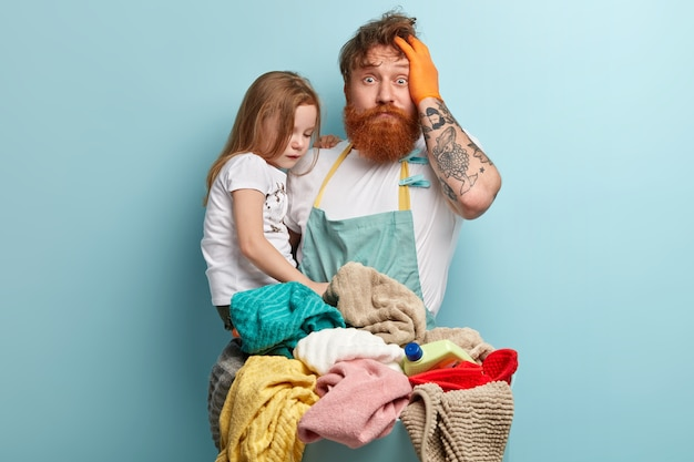 Man with ginger beard holding his daughter and doing laundry