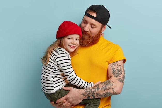 Uomo con la barba allo zenzero che tiene sua figlia
