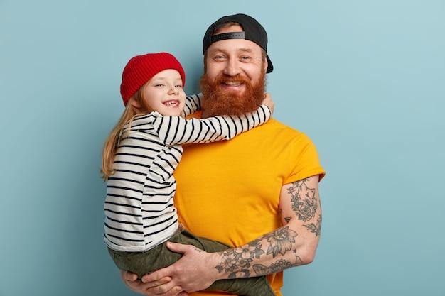 Мужчина с рыжей бородой держит свою дочь