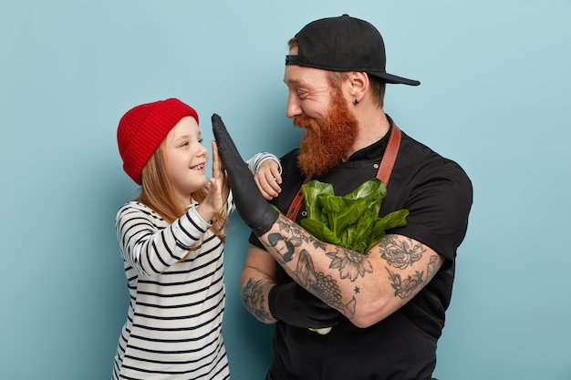 エプロンと手袋で生姜のひげを生やした男が娘をハイタッチ