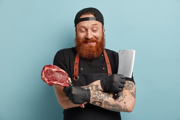 앞치마에 생강 수염과 칼과 고기를 들고 장갑을 가진 남자