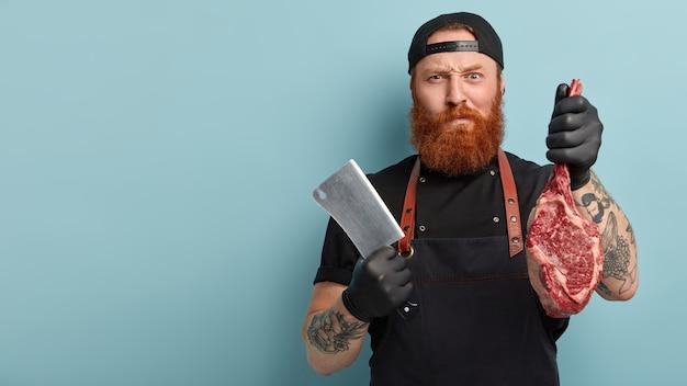 Мужчина с рыжей бородой в фартуке и перчатках держит нож и мясо