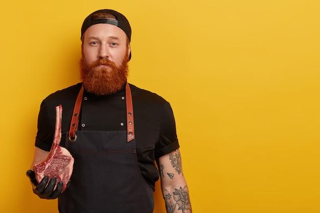 Мужчина с рыжей бородой в фартуке и перчатках держит мясо