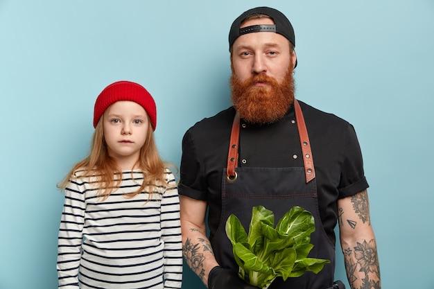 エプロンと手袋で生姜のひげを持った男が娘の隣にサラダを持っている