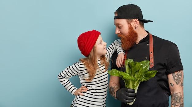 エプロンで生姜のひげと娘とポーズをとる手袋を持つ男