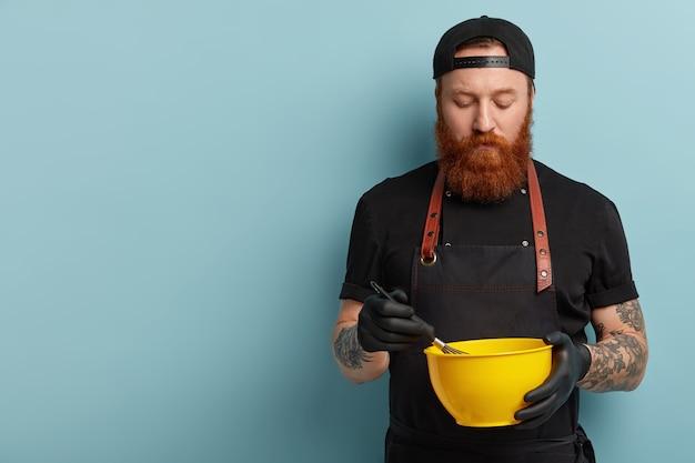 Мужчина с рыжей бородой в фартуке и перчатках держит миску