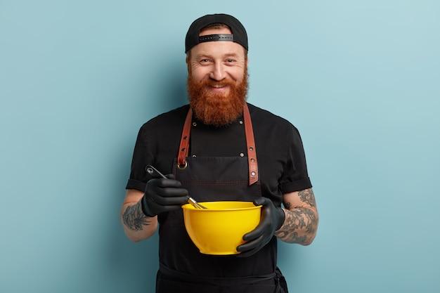 Uomo con barba allo zenzero che indossa grembiule e guanti tenendo la ciotola
