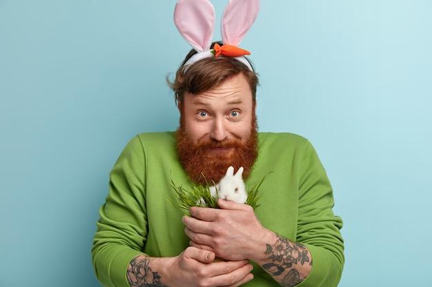Человек с рыжей бородой в яркой одежде и кроличьими ушками держит кролика