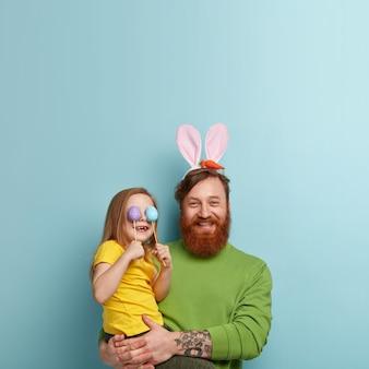 カラフルな服と彼の娘を保持しているバニーの耳を身に着けている生姜のひげを持つ男