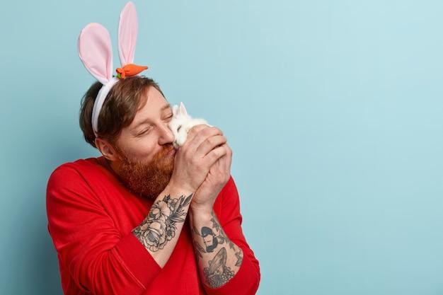 Человек с рыжей бородой в яркой одежде и кроличьих ушах