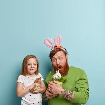화려한 옷을 입고 생강 수염을 가진 남자와 토끼를 들고 그의 딸