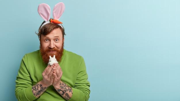 Uomo con barba allo zenzero che indossa abiti colorati e orecchie da coniglio che tiene il coniglietto