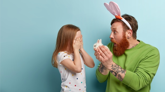 Man with ginger beard wearing colorful clothes and bunny ears holding bunny