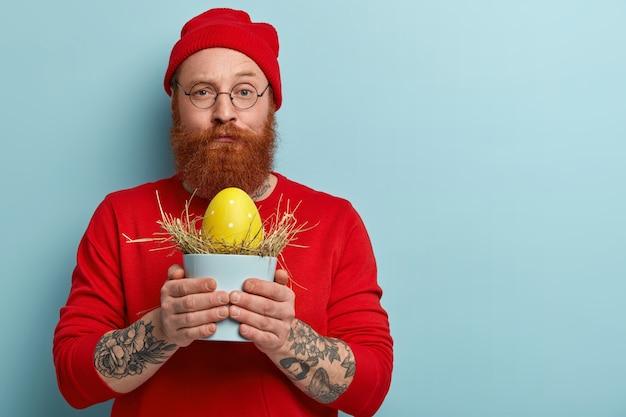 Мужчина с рыжей бородой в яркой одежде держит пасхальное яйцо