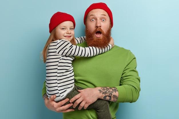 Uomo con la barba allo zenzero che indossa abiti colorati che tiene sua figlia