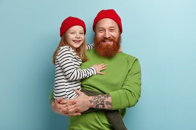 Человек с рыжей бородой в яркой одежде и держит свою дочь