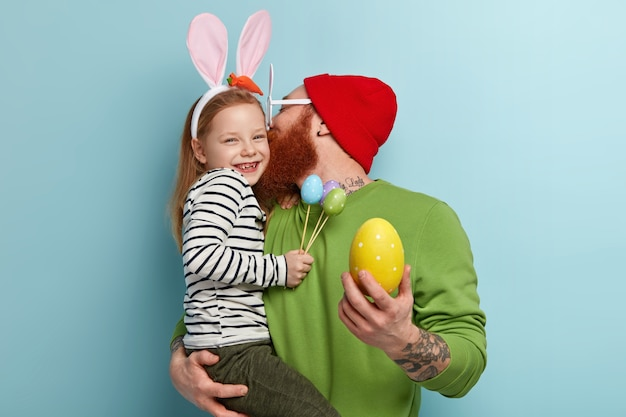 Man with ginger beard wearing colorful clothes holding his daughter