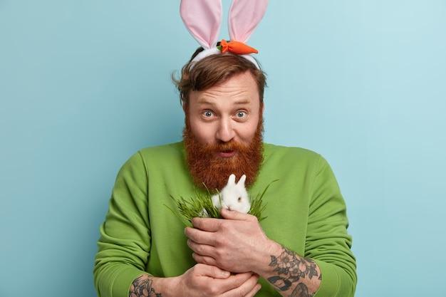 Человек с рыжей бородой в яркой одежде и держит кролика