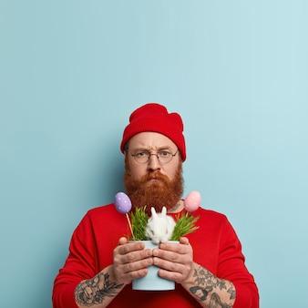 Uomo con la barba allo zenzero indossando abiti colorati e tenendo il coniglio