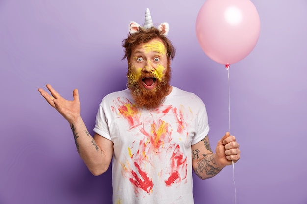 Мужчина с рыжей бородой в повязке на голову единорога и грязной футболке