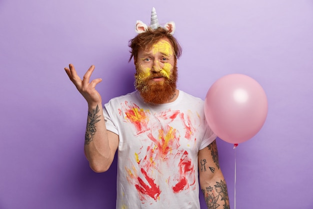 Man with ginger beard wearing unicorn headband and dirty t-shirt