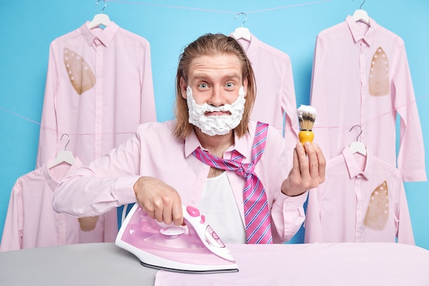 Man with ginger hair uses brush for applying shaving gel stands near ironing board strokes wrinkled clothes dresses for work