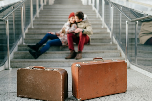 Man with girlfriend, suitcases wait for train on stairs.