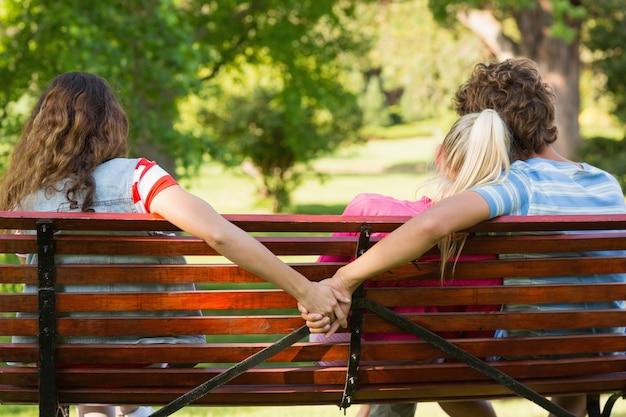 Человек с подругой, держась за руки с другой женщиной