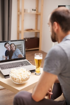 Uomo con un bicchiere di birra sul tavolo in videochiamata con i suoi amici durante il distanziamento sociale.